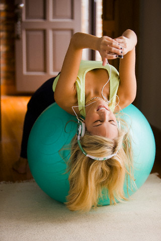 Smiling woman using MP3 player while exercising with a balance ball
