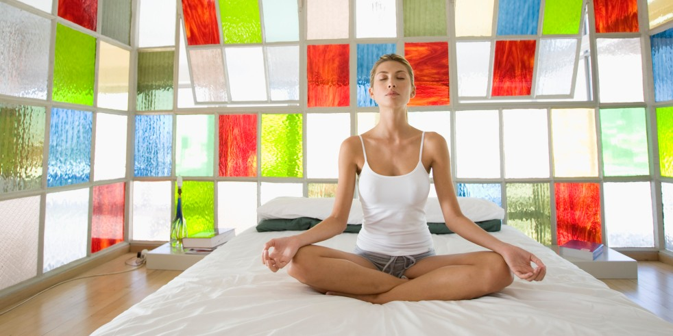 Young woman doing yoga on bed