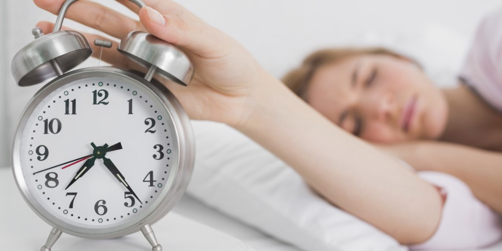 Blonde lying in bed and hitting alarm clock